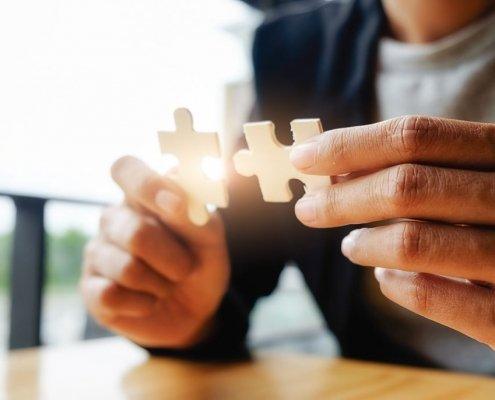 Personne qui tiens dans sa main 2 pièces de puzzle