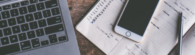 Ordinateur portable à coté du quel se trouve un téléphone et un cahier avec des note et un stylo