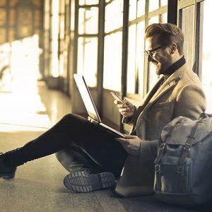 Homme assis avec son sac et son laptop